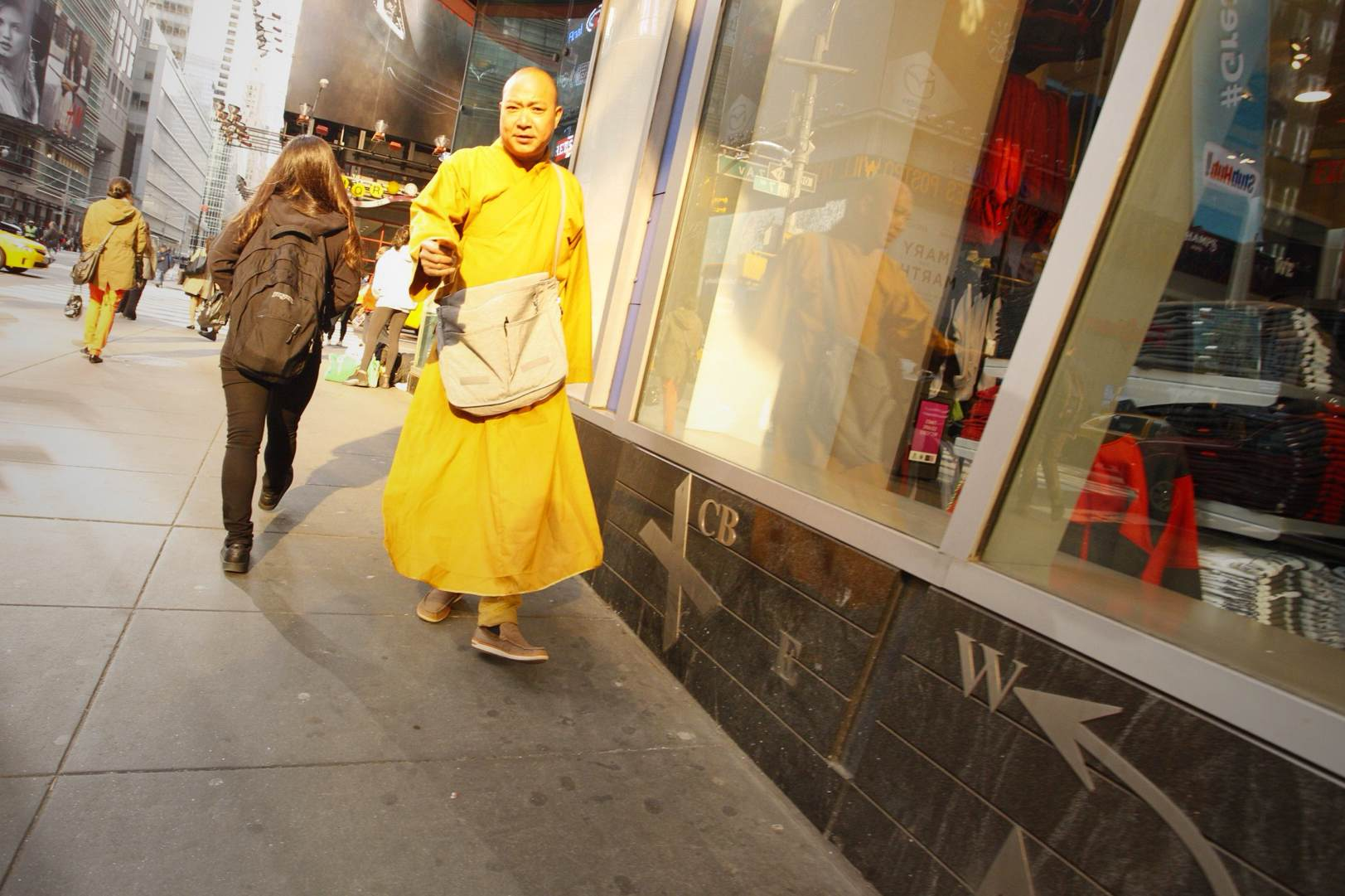 The warm glow of the early morning sun illuminates a Monk's robe near Times Square.