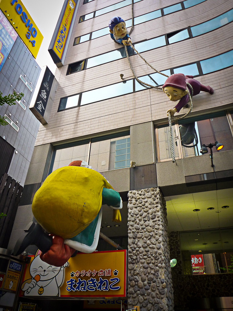 Santa climbing a building with help from his elves