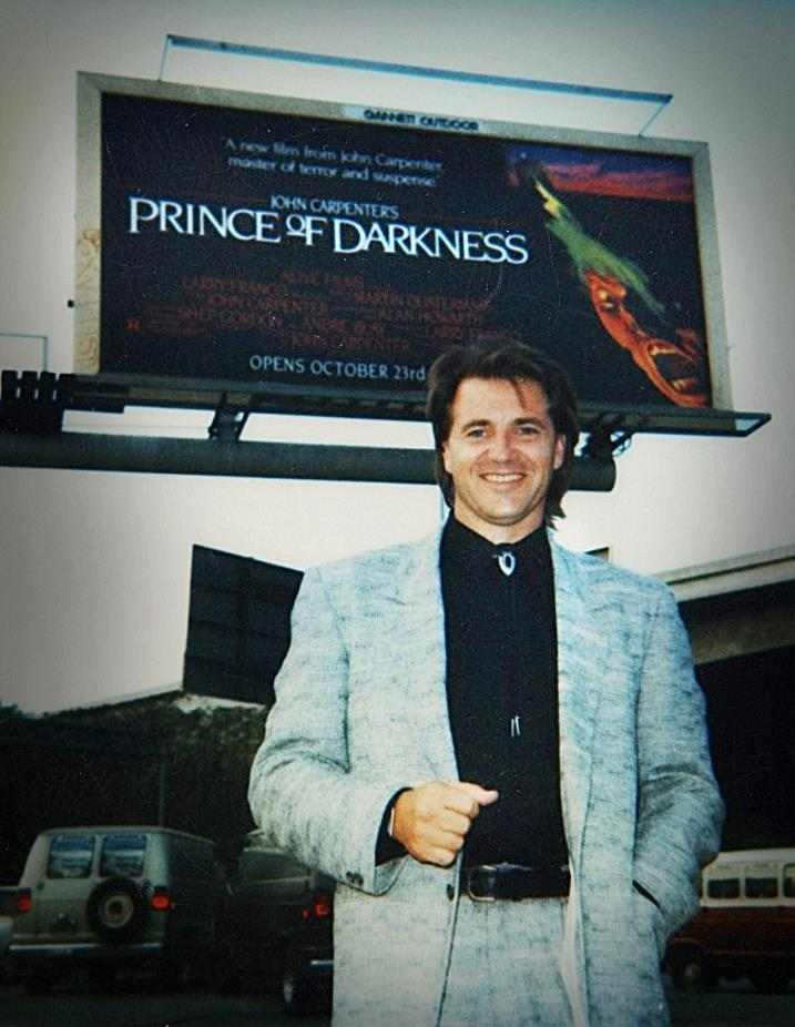 On Hollywood Blvd in front of the billboard for Prince of Darkness