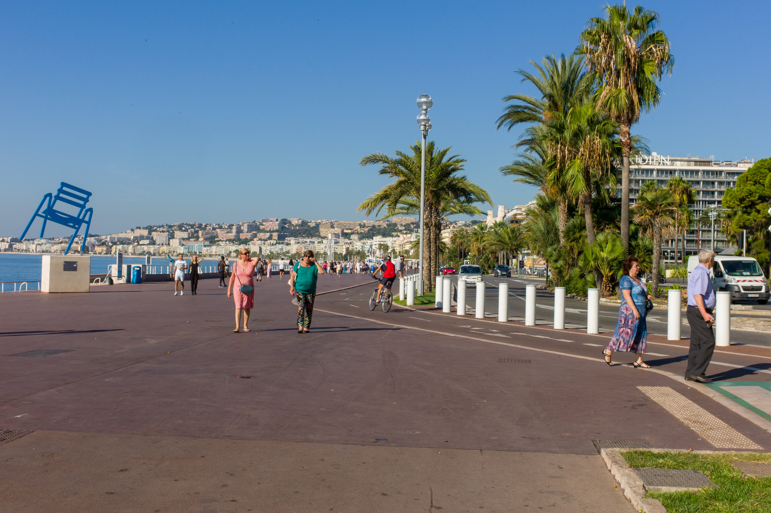 Promenade des Anglais, Nice, France, 2018  Starting in the second half of the 18th century, the English aristocracy took to spending the winter in Nice, enjoying the panorama along the coast. Inspecting this image, our eyes may land first on the people. The promenade might be second simply because of its weight in the image. The odd alignment of the chair might also attract attention. The subtlety (or punctum) however relates to the white posts along the edge of the promenade. They protect the strollers from traffic. On July 14, 2016 a truck was deliberately driven down the promenade, killing 84 people and injuring over 200.