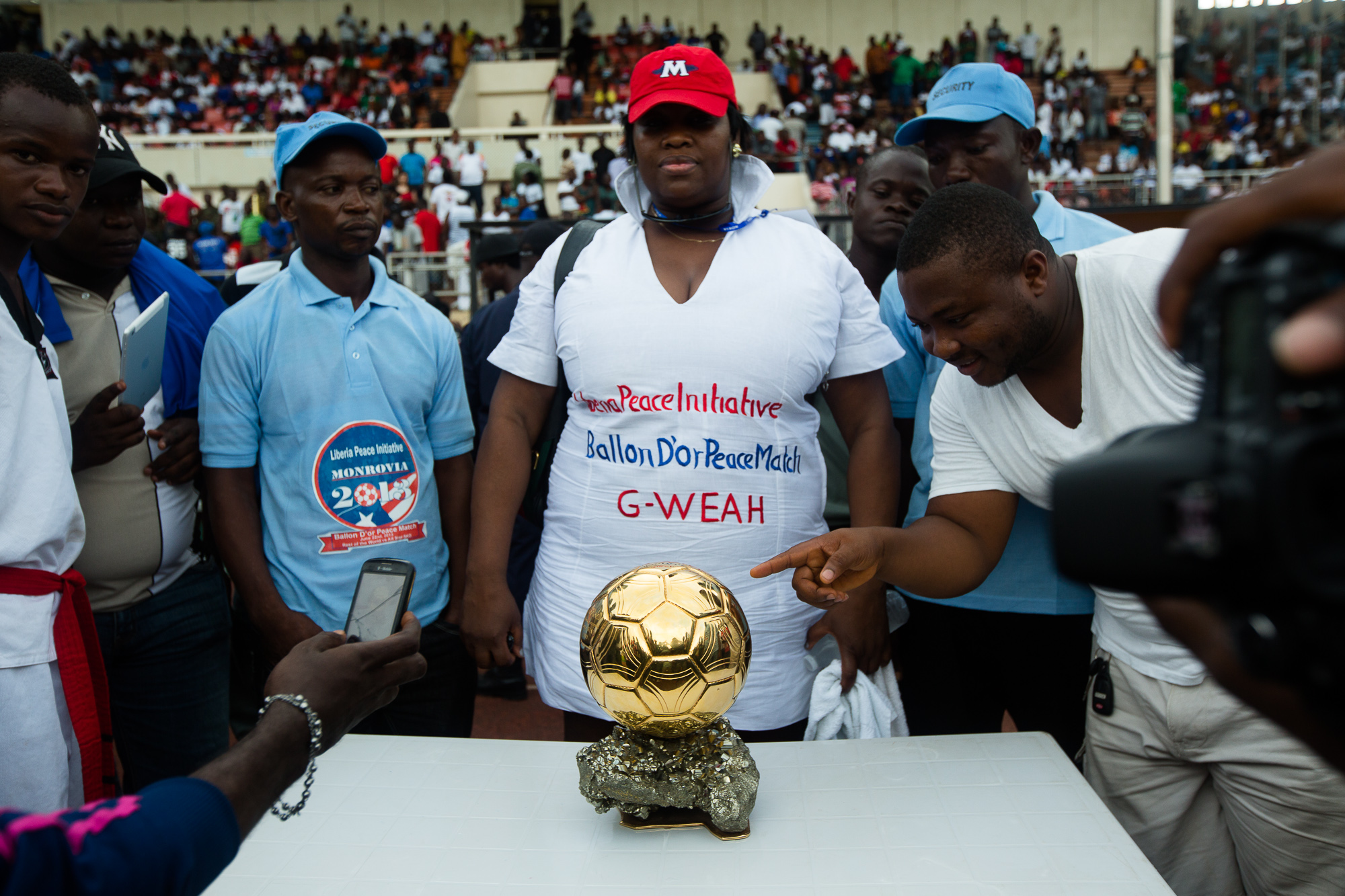 Monrovia, Liberia - June 22, 2013: A representative from Leymah Gbowee's Peace Initiative guards Weah's 1995 Fifa World Player of the Year trophy at the Peace Football Match at the Samuel K. Doe Sports Complex.