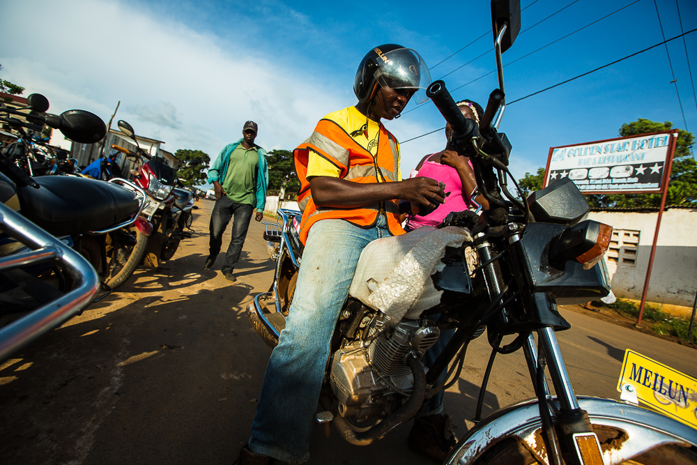 Monrovia, Liberia - November 13, 2013: Drivers support government regulations to require neon vests, helmets, and proper shoes to increase safety. It was rare to see any of these before, but the number of helmets and vests are steadily increasing. Photo by Morgana Wingard