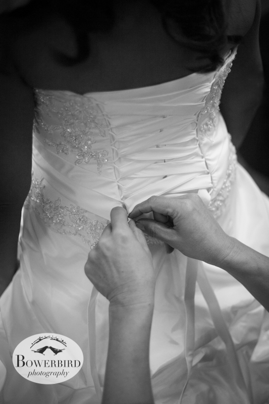 Roselle's mom ties the lace back of her beautiful wedding dress.© Bowerbird Photography 2012; Wedding Photography in Dublin, CA.