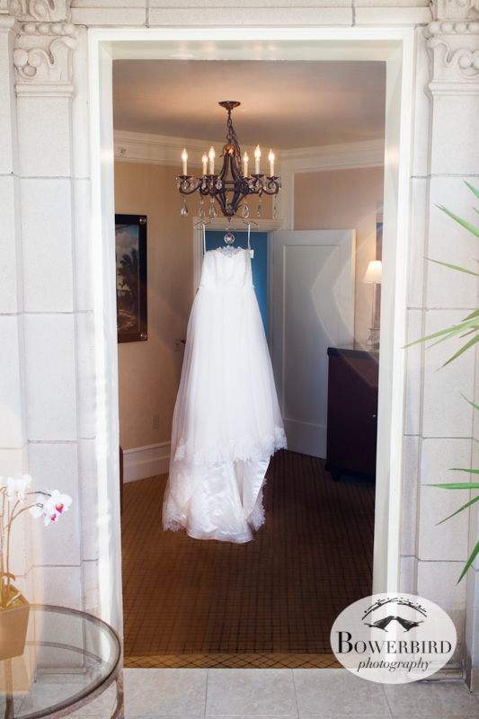 "T he bride's wedding dress, called ""High Society,"" hangs on a chandelier. © Bowerbird Photography 2013; Mark Hopkins Hotel, San Francisco."
