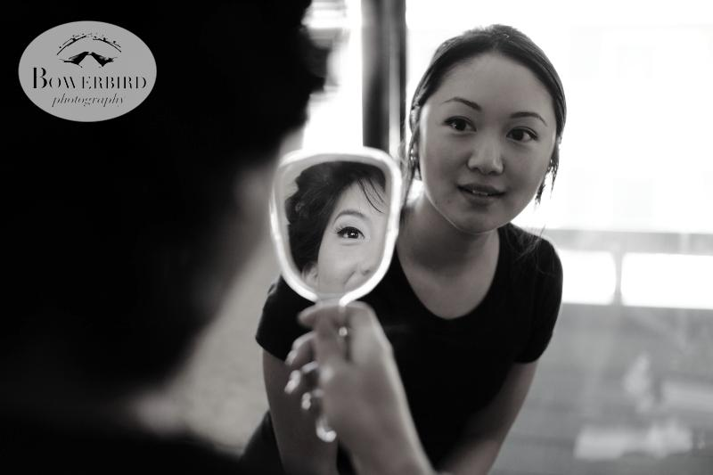 The bride looks at herself in a small mirror. ©Bowerbird Photography 2013; St. Ignatius Church Wedding, San Francisco.