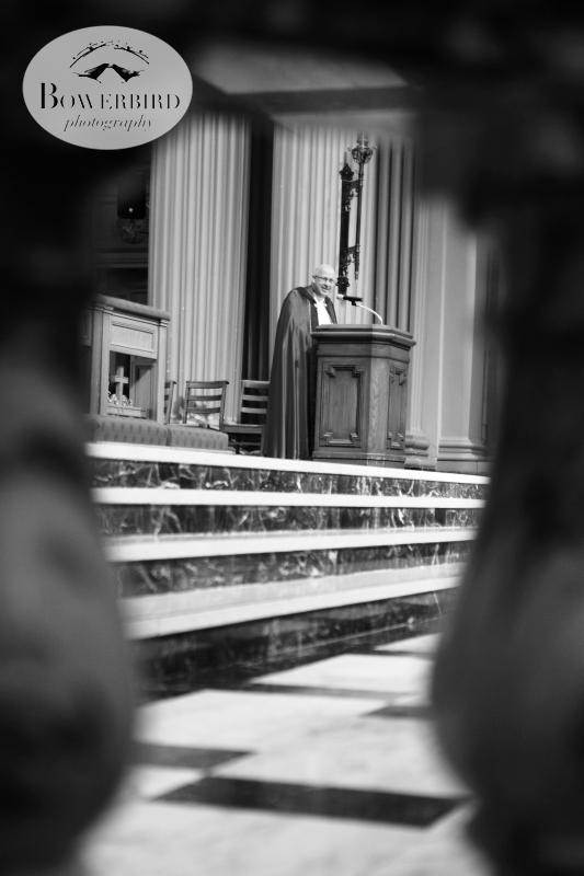 The minister reading a prayer during the wedding ceremony. ©Bowerbird Photography 2013; St. Ignatius Church Wedding, San Francisco.