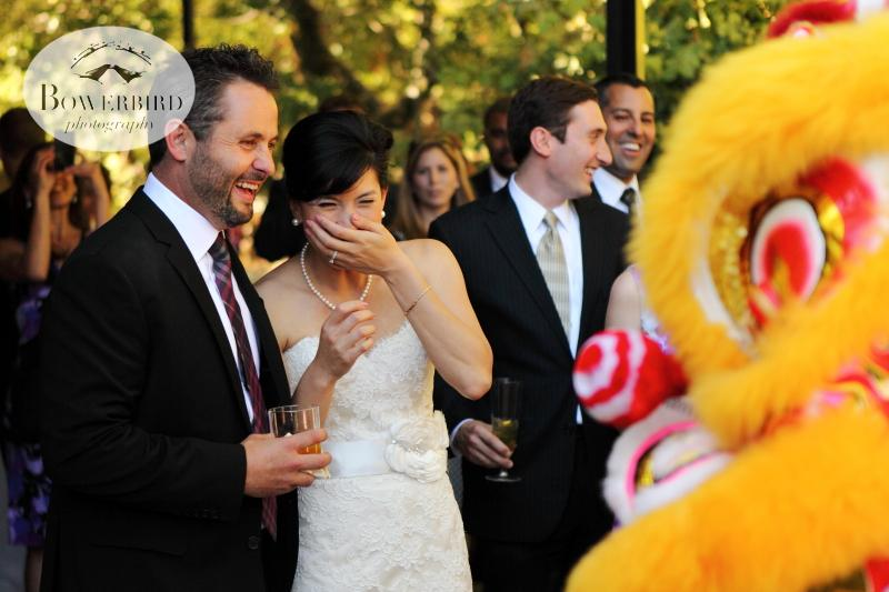 The bride and groom, watching the lion dancers at their wedding. ©Bowerbird Photography 2013; Marin Art and Garden Center Wedding, Ross, CA.