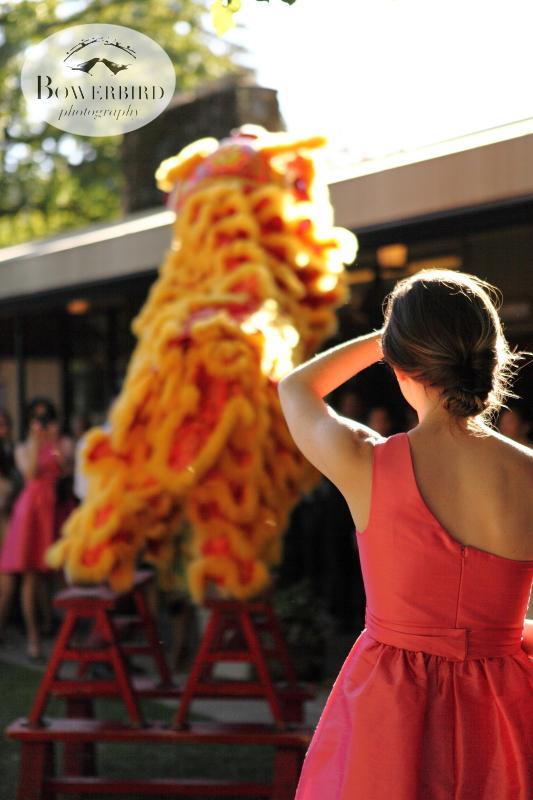 A bridesmaid watches the lion dance. ©Bowerbird Photography 2013; Marin Art and Garden Center Wedding, Ross, CA.