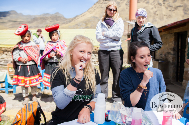 Students from SUNY Brockport, conducting a tooth brushing demonstration at the dental hygiene station. © Bowerbird Photography 2013, Sacred Valley Health and Suny Brockport in Yanamayo, Peru.