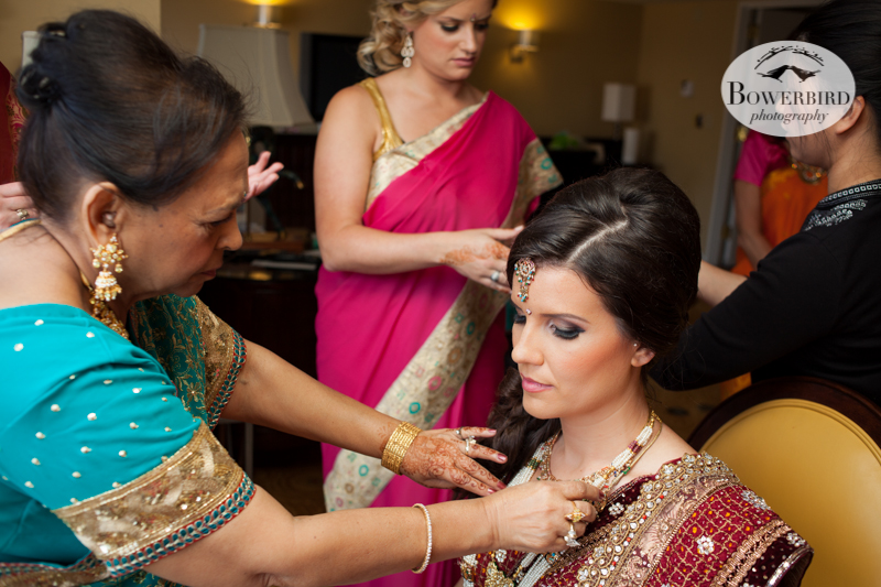 The groom's mom helps the bride put on her jewelry and gold. © Bowerbird Photography 2013, South Asian Wedding at the San Francisco JW Marriott and Winery SF on Treasure Island.