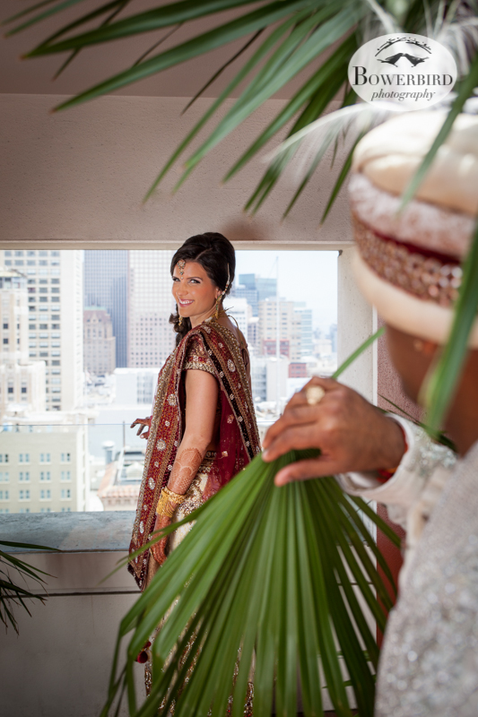 The bride looks out over the San Francisco cityscape, and the groom peeks between palm fronds to admire his bride.© Bowerbird Photography 2013, First Look, South Asian Wedding at the San Francisco JW Marriott and Winery SF on Treasure Island.