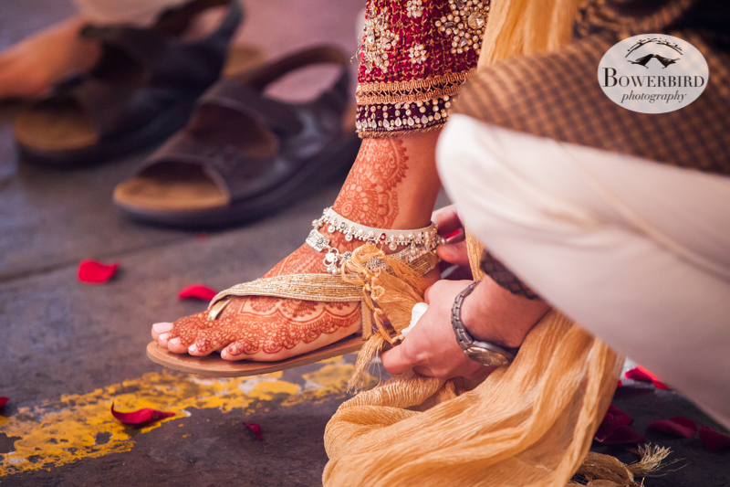 Angelica's brother helping her take off her sandals to enter the ceremony platform. © Bowerbird Photography 2013, South Asian Wedding at the San Francisco Winery SF on Treasure Island.