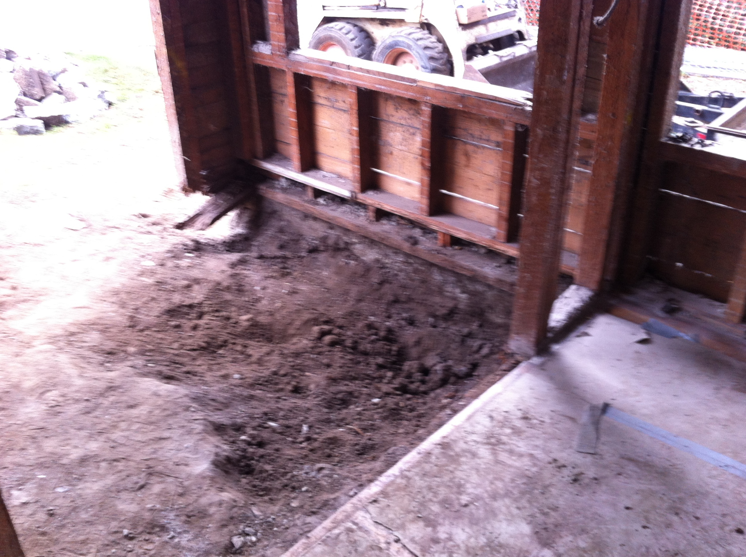 This is why there were termites. The old entry was an even older(?) porch with a concrete floor. The dirt underneath was up against the floor framing.
