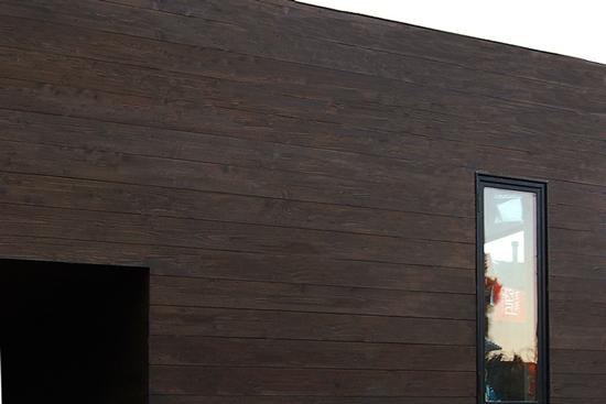construction photos: casement window at modern dark-stained cedar siding