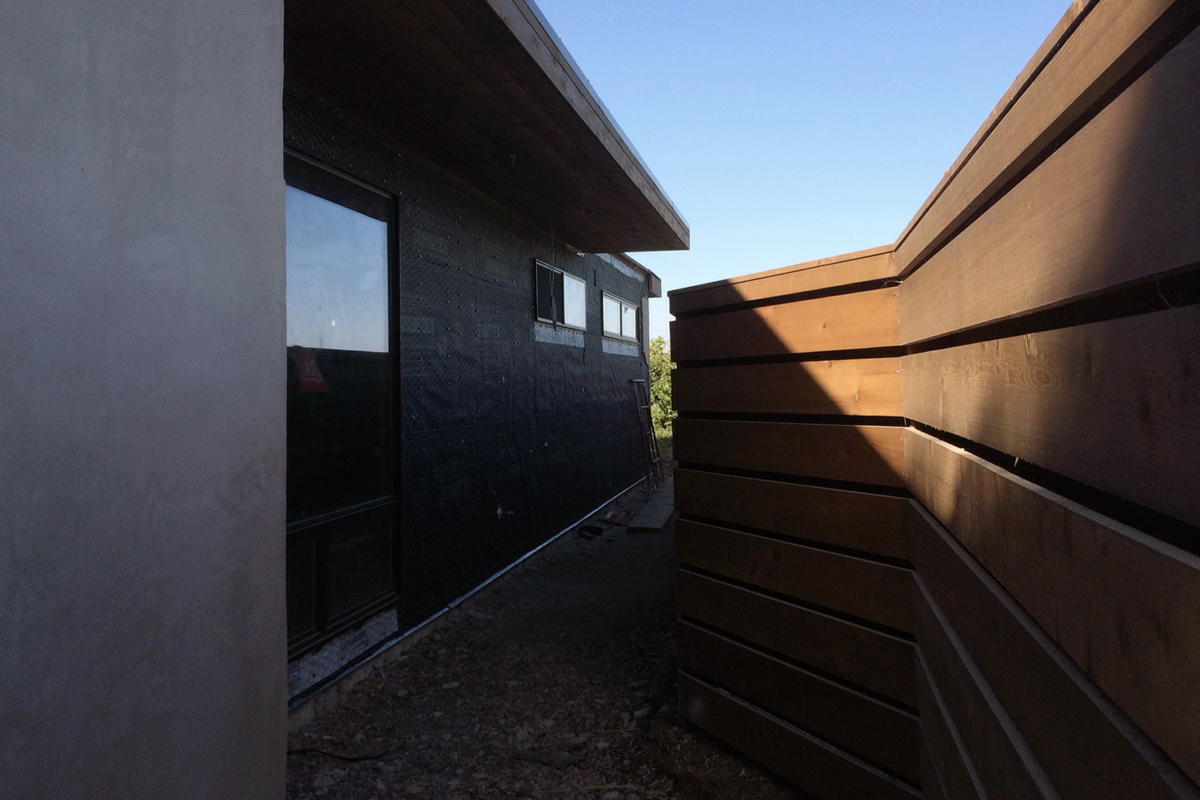 new cedar fence + awning / smooth stucco + lath / metal windows