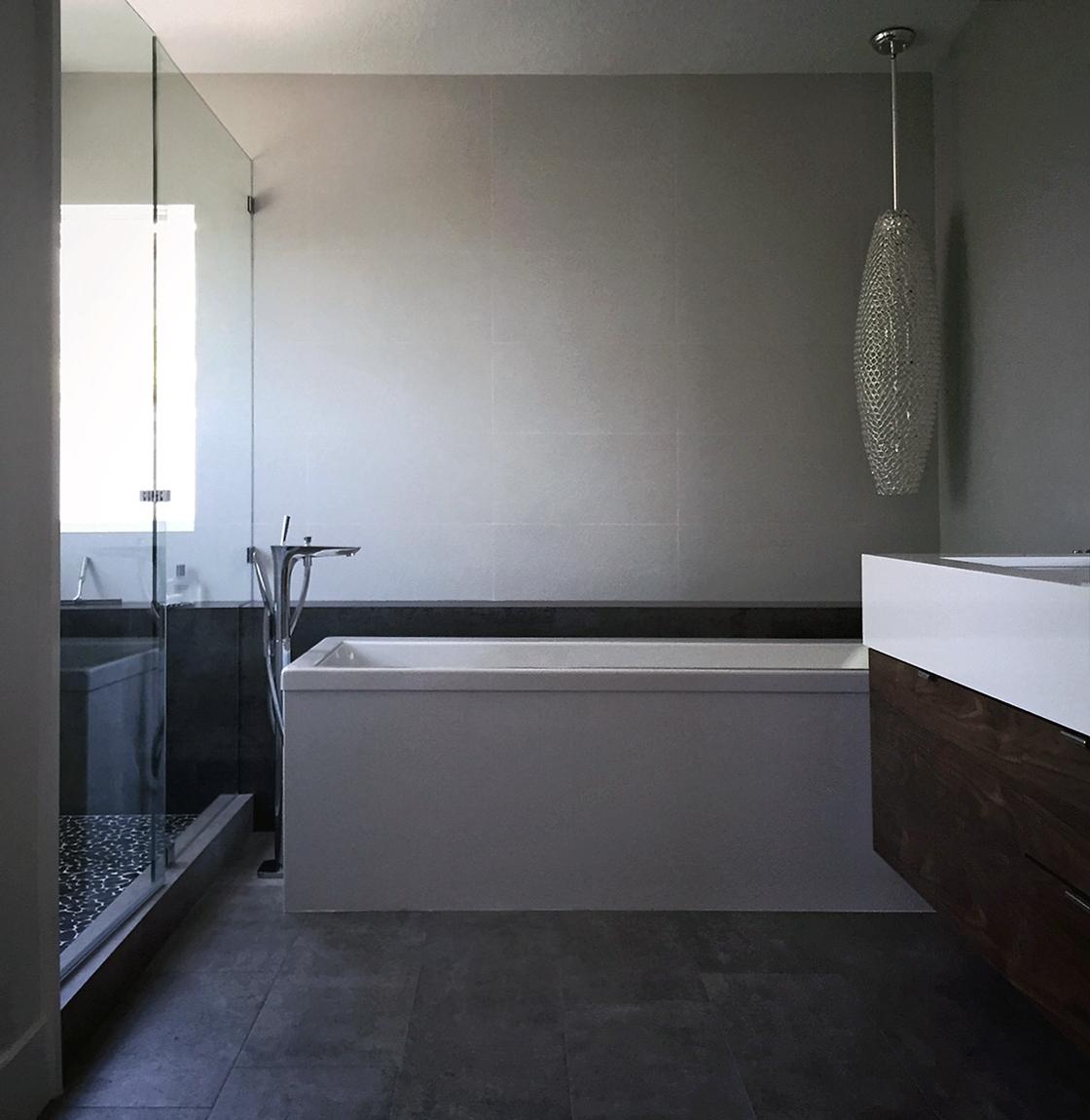 freestanding bath at cantilevered walnut vanity