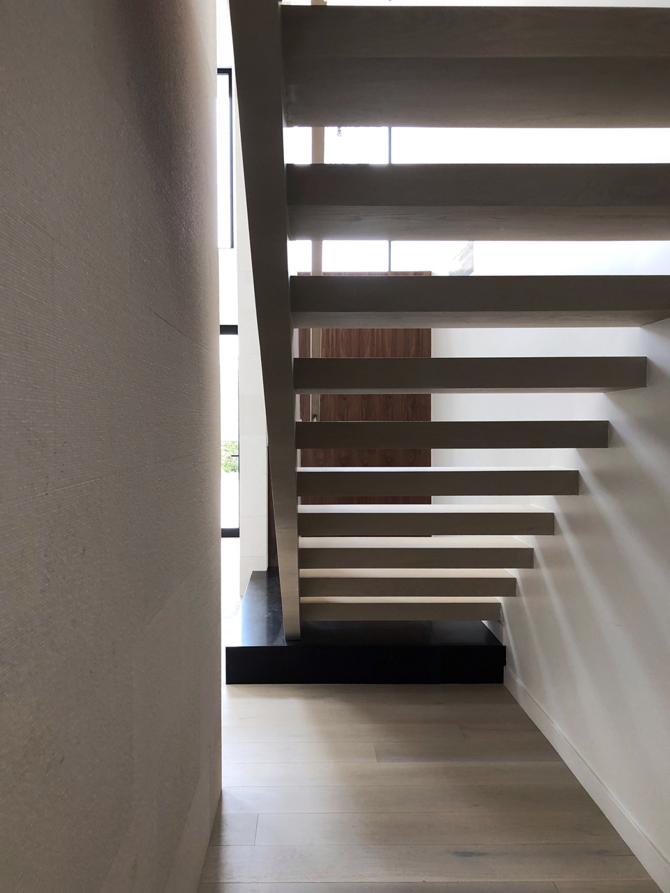 floating oak stair at limestone wall / view from hallway