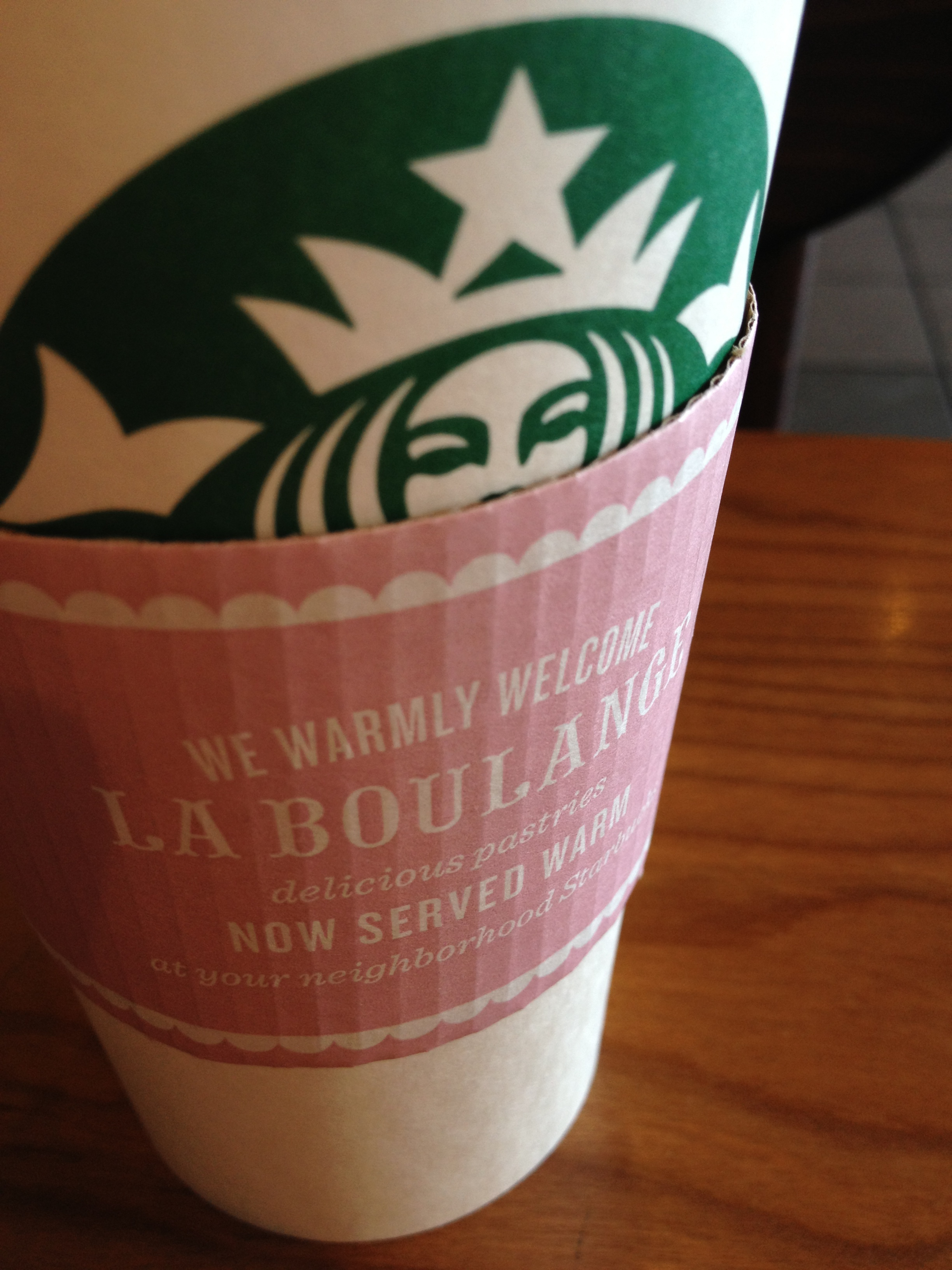 New cup sleeve at Starbucks welcoming La Boulange. Design clash.