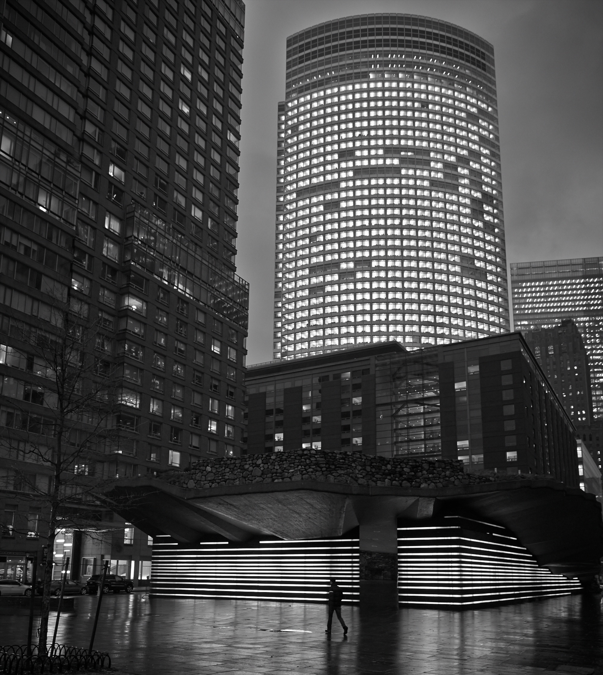 The  Irish Hunger Memorial , a public art installation in Battery Park City, lies in the shadow of the glowing headquarters of Goldman Sachs.