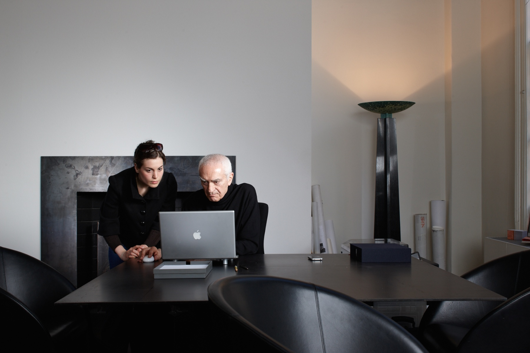 Massimo working with one of his designers at the incredibly uncluttered desk where he did much of his design.