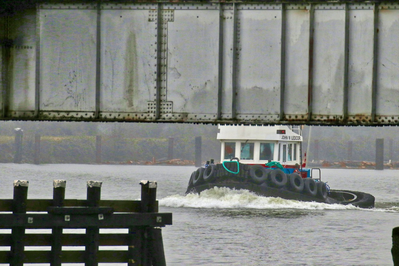 """Tugboat """"JOHN M LEDCOR"""" approaches the North Arm rail swing bridge in the Fraser River on January 8, 2018. Although it may not look like it, the bridge was open for marine navigation when this photo was taken.  Click image to enlarge."""