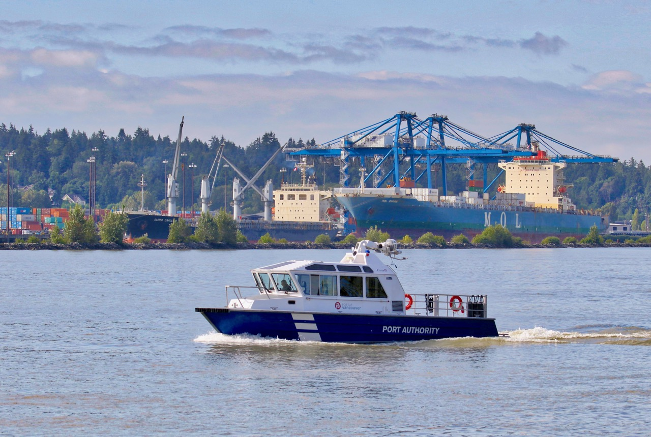 """Vancouver Port Authority patrol boat near Fraser Surrey Docks in Fraser River.   Cargo ships """"SUPER CAROLINE"""" and """"MOL EMPIRE"""" are docked at the port."""