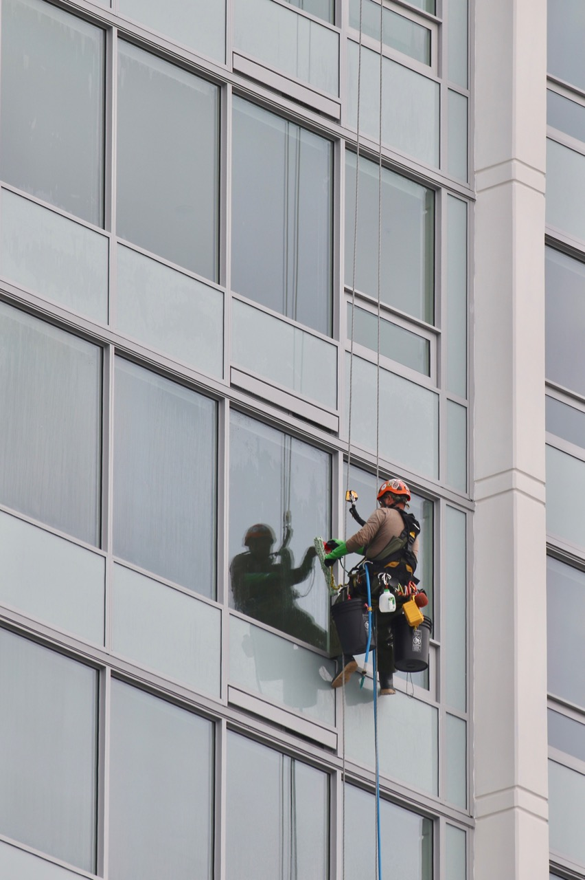Window washer and reflection at RiverSky, New Westminster B.C.