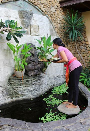 Wayan placing offering at Dragon Lounge