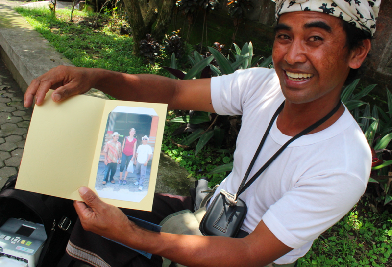 Balinese guy selling photo of familiar very tall white girl with short Javanese tourists to said Javanese tourists