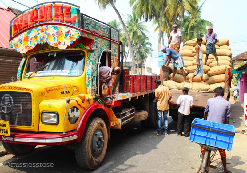 Navigating the narrow roads of Fort Kochi while sacks of ginger are loaded onto a truck