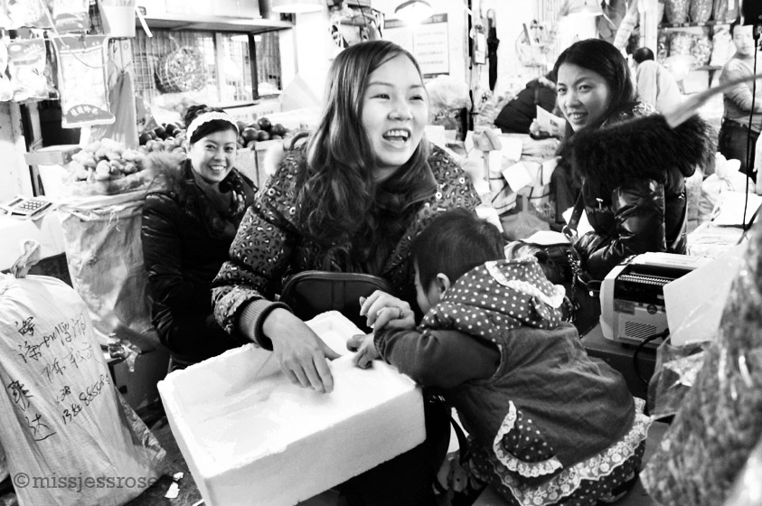 Hiding from the camera amidst the narrow aisles of Qing Ping market