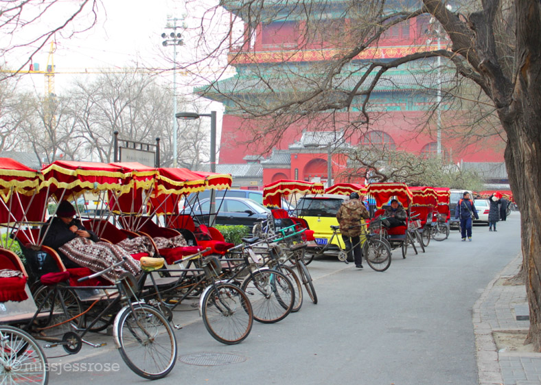 Red rickshaws sitting empty in the wintertime, waiting to give tourists a ride around the hutong