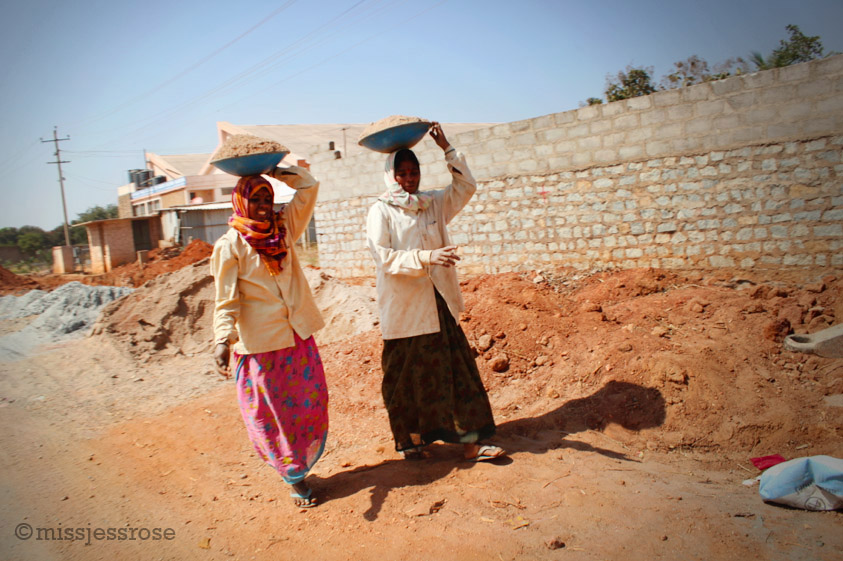 More female construction workers carrying bowls of gravel on their head (Photo by: C. Paine)