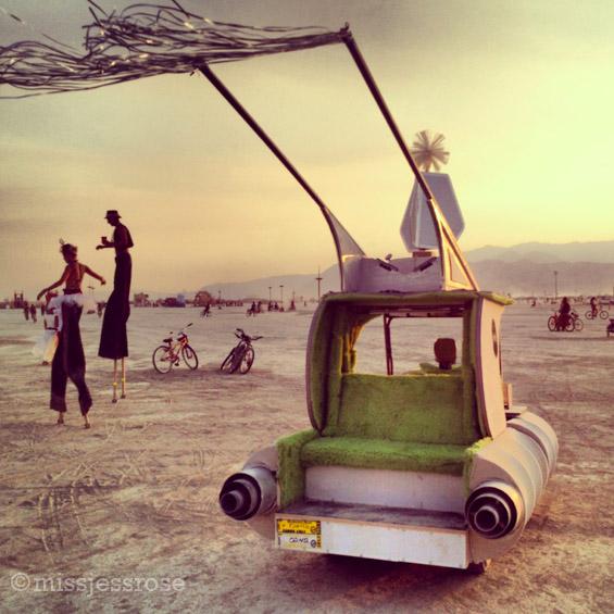 Stilt walkers at sunset and an art car