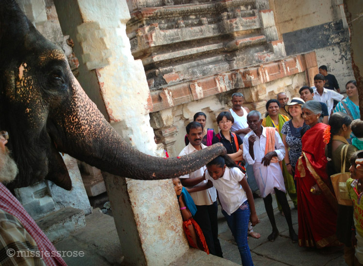 Lakshmi gives a blessing as a crowd looks on