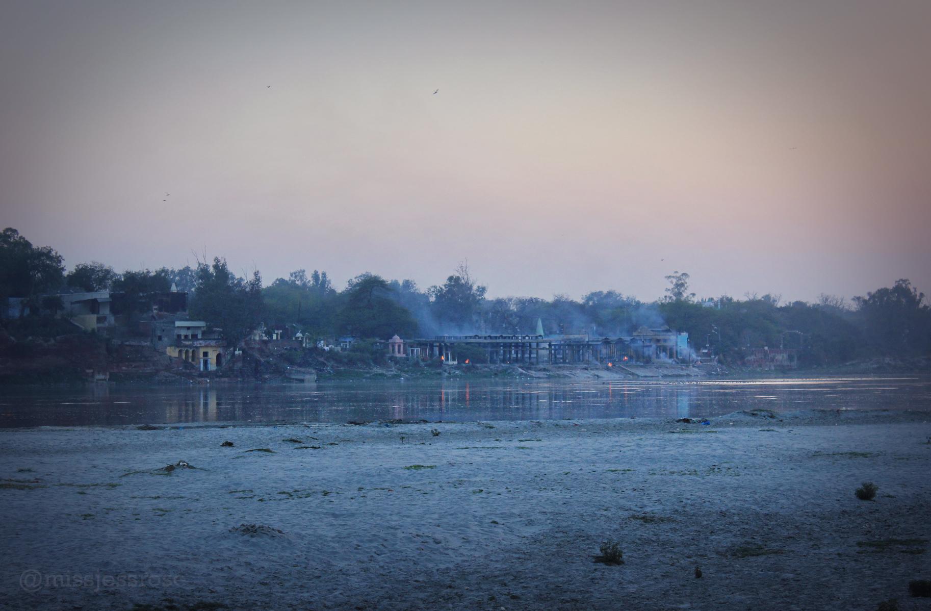 Fires burning alongside the Yamuna river near the Taj at dusk