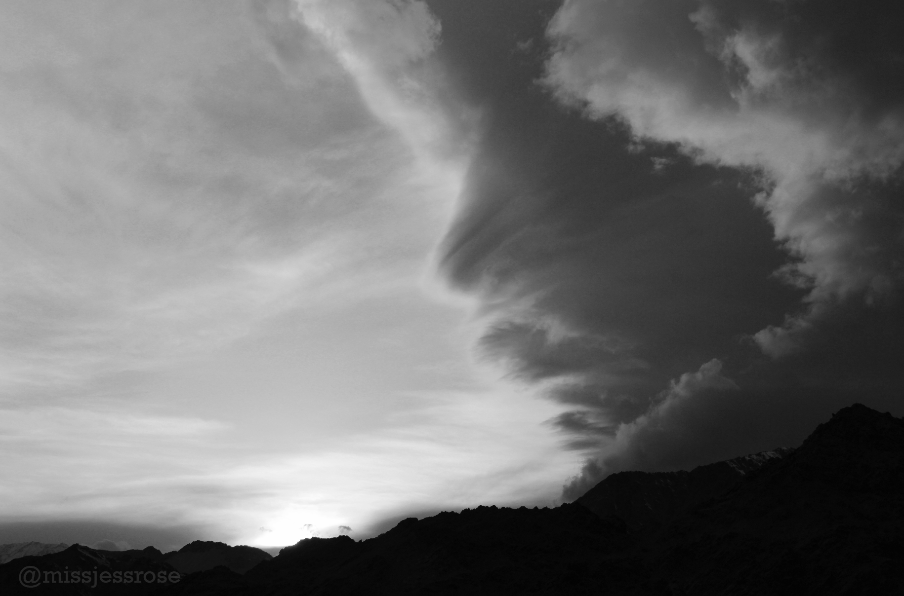 Dramatic clouds roll in as the sun begins to set behind the Himalayan Mountains.
