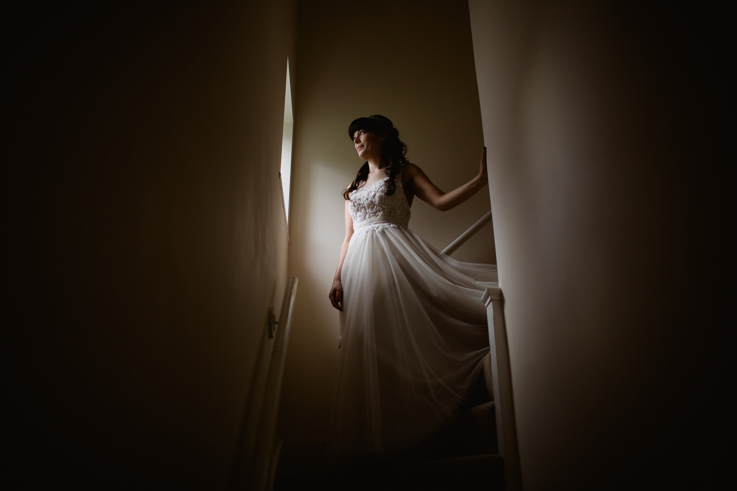 Bridal portrait - long bridal gown -  window lit bride - Birmimgham wedding - Bride on the stairs