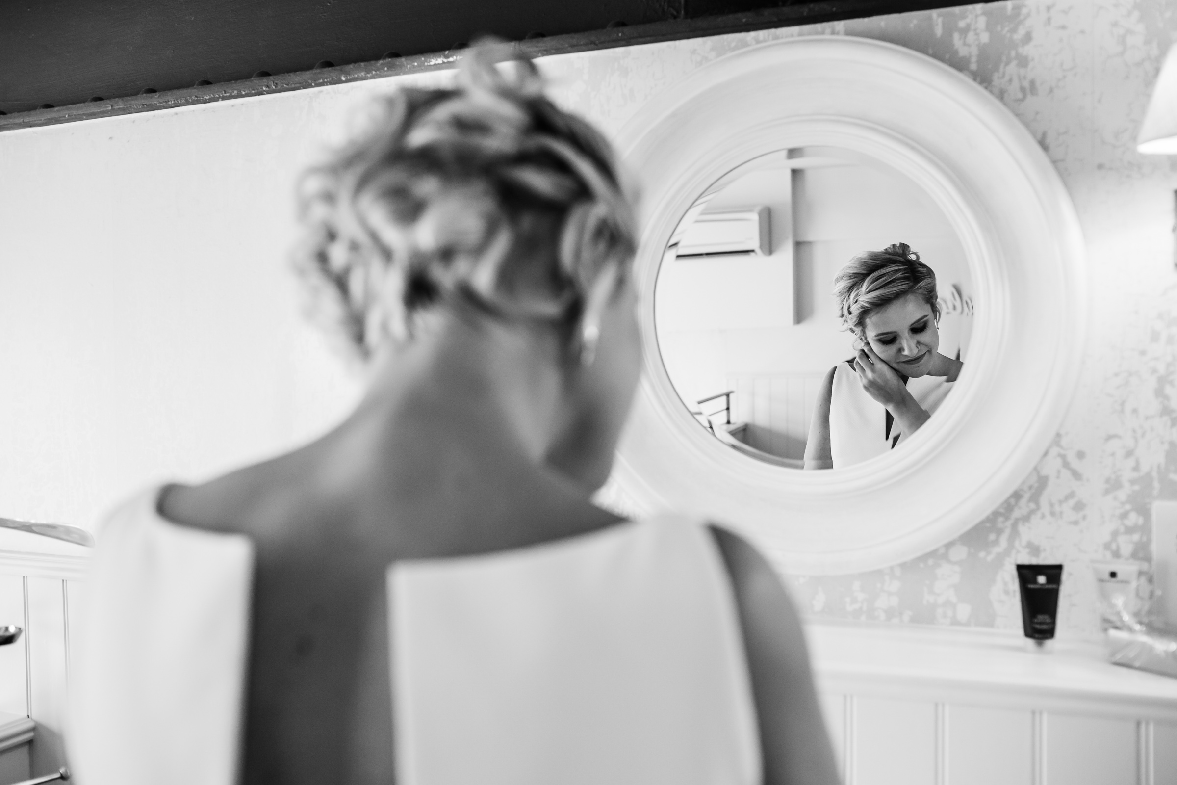 a bride puts on earrings at great john street hotel manchester
