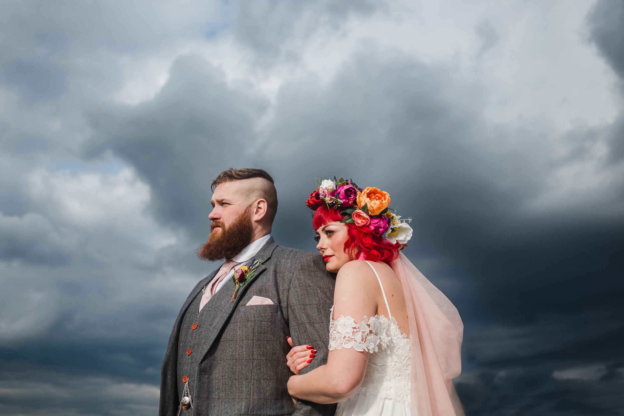 An alternative bride and groom cuddle up under a grey sky outside the Compasses at Pattiswick