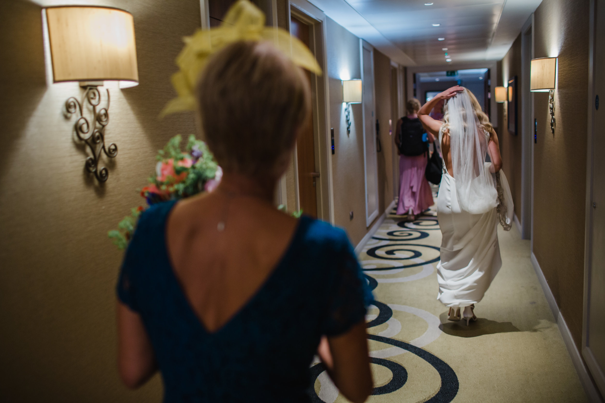 Bridal party running down the corridor of the Clayton Hotel Birmimgham