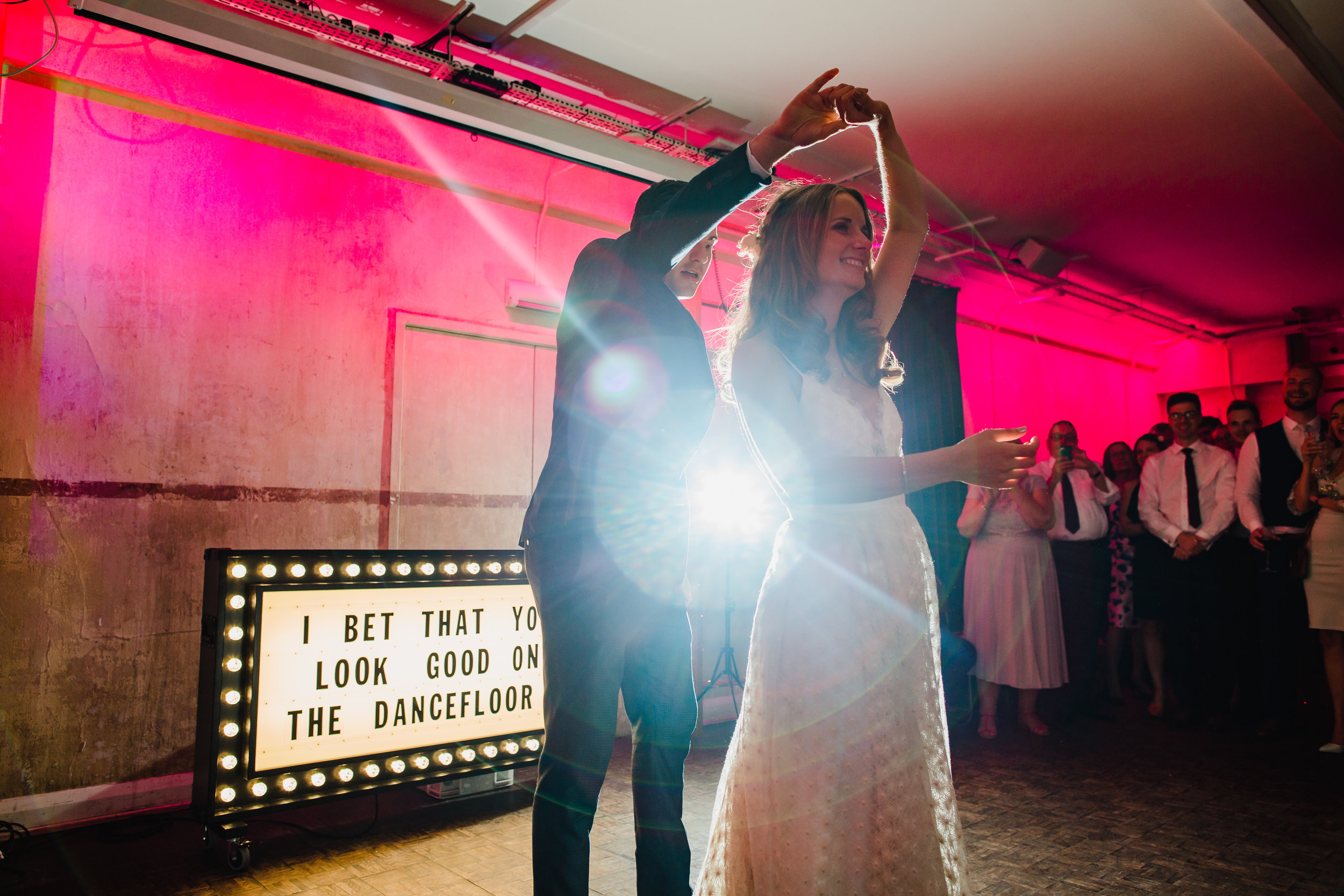A bride and groom dance in front of a light up sign in Tanner Warehouse London