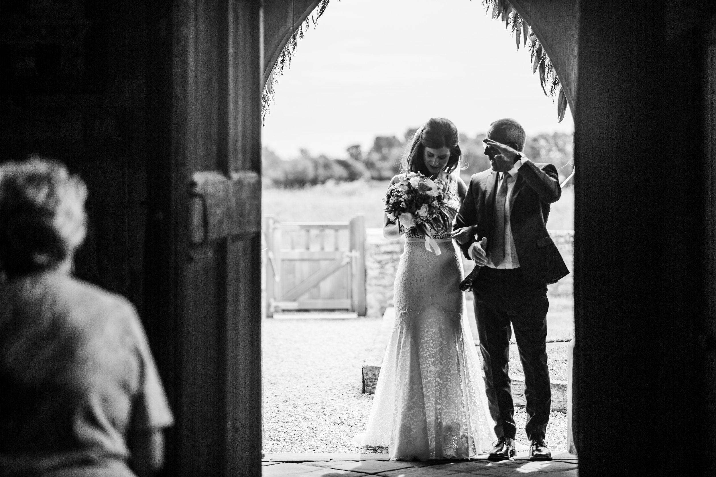 A bride waits with her dad in the entrance of a church.