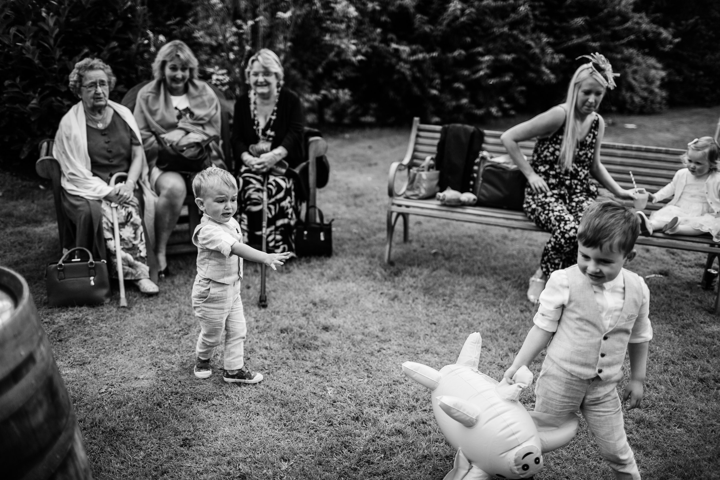 children play with inflatable pigs at a wedding