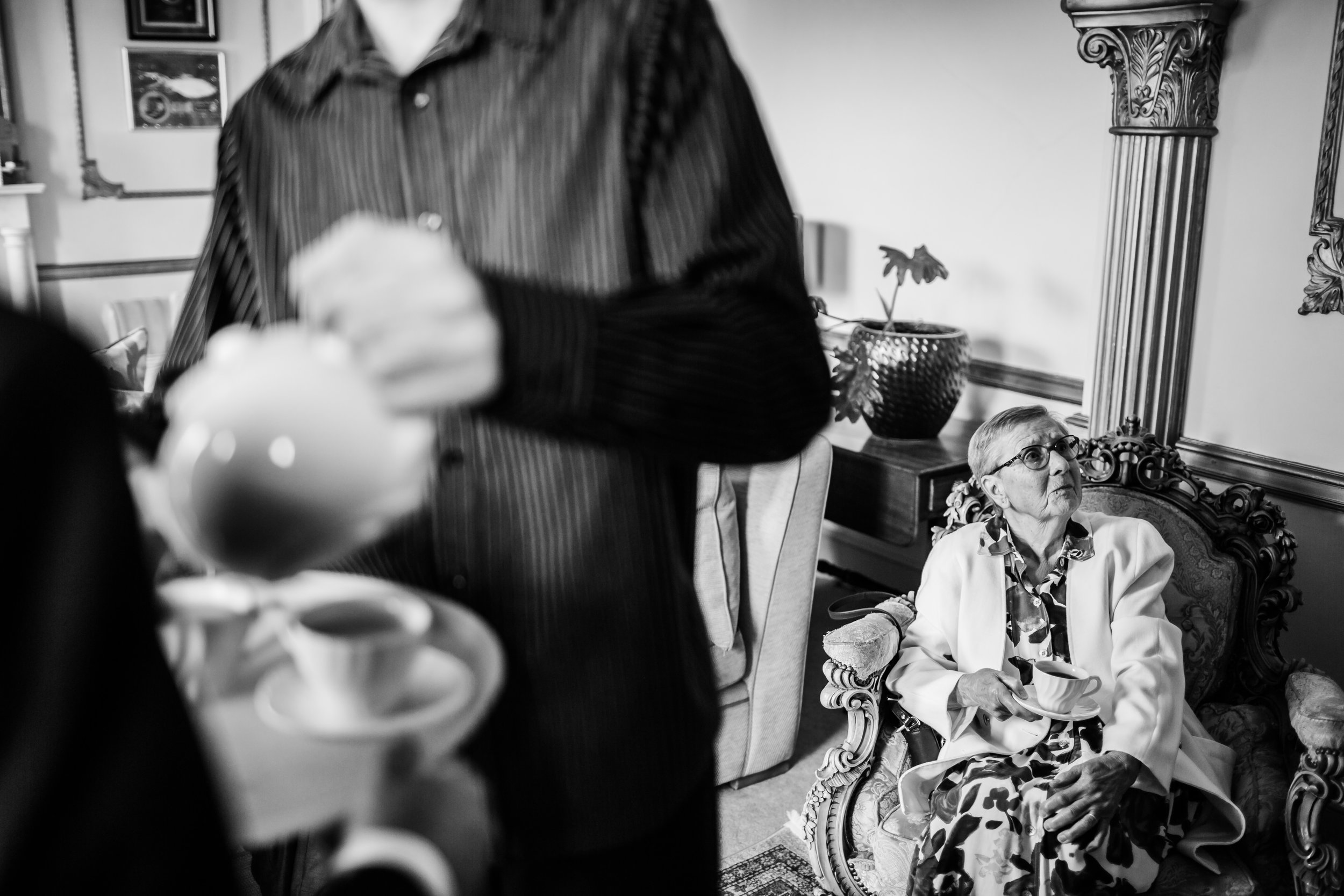 a man pours tea while gran drinks her tea behind him at a wedding