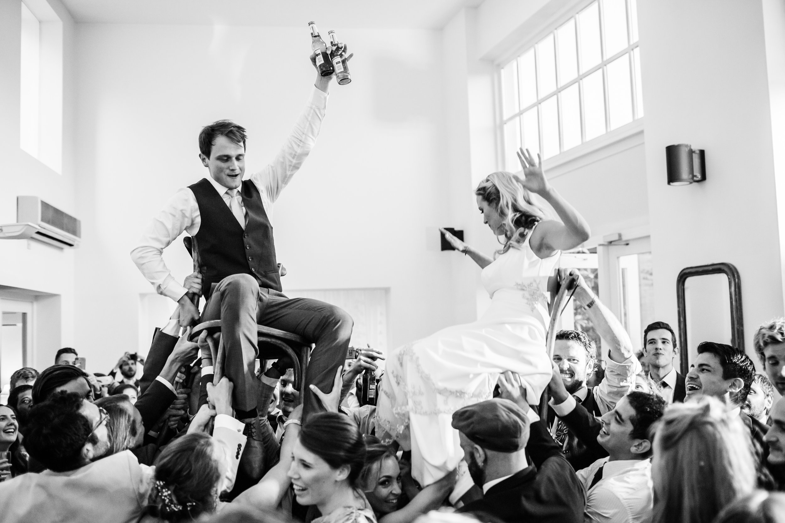 a bride and groom are carried on chairs at Fazeley Studio.