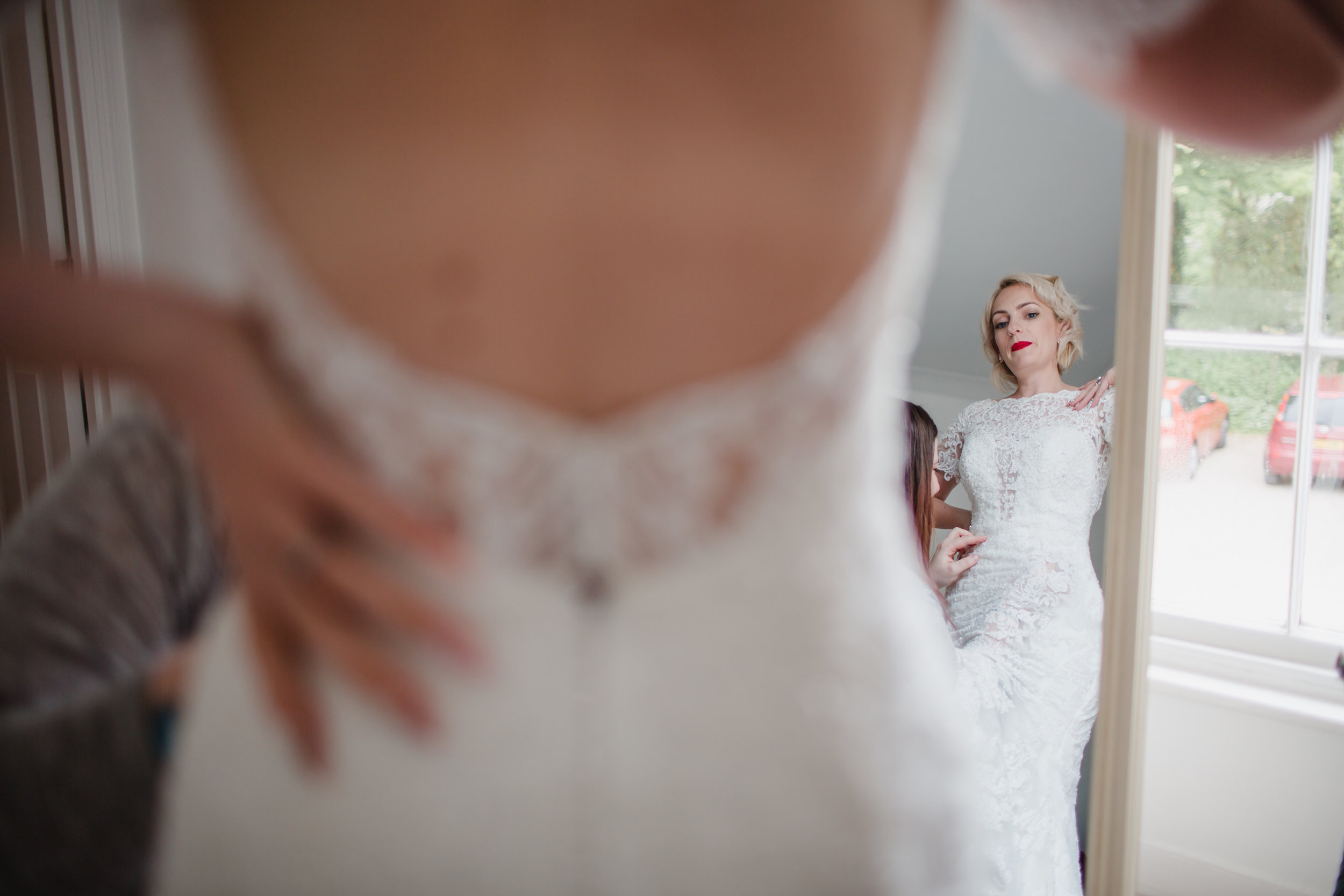 a bride looks at herself in a mirror at rosevine hotel truro cornwall
