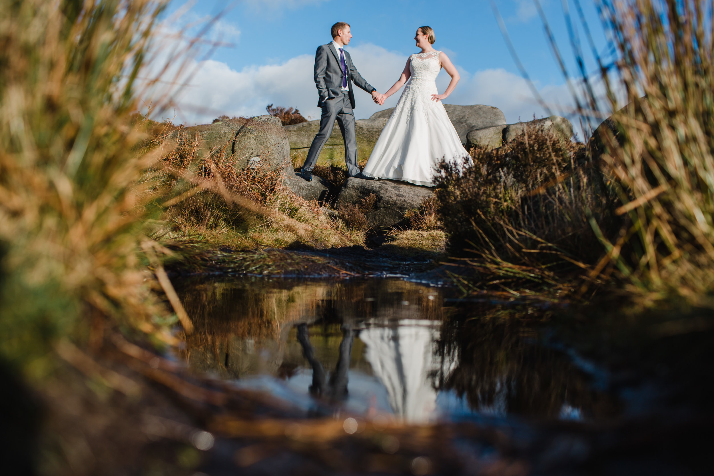 a bride and groom reflected in a puddle