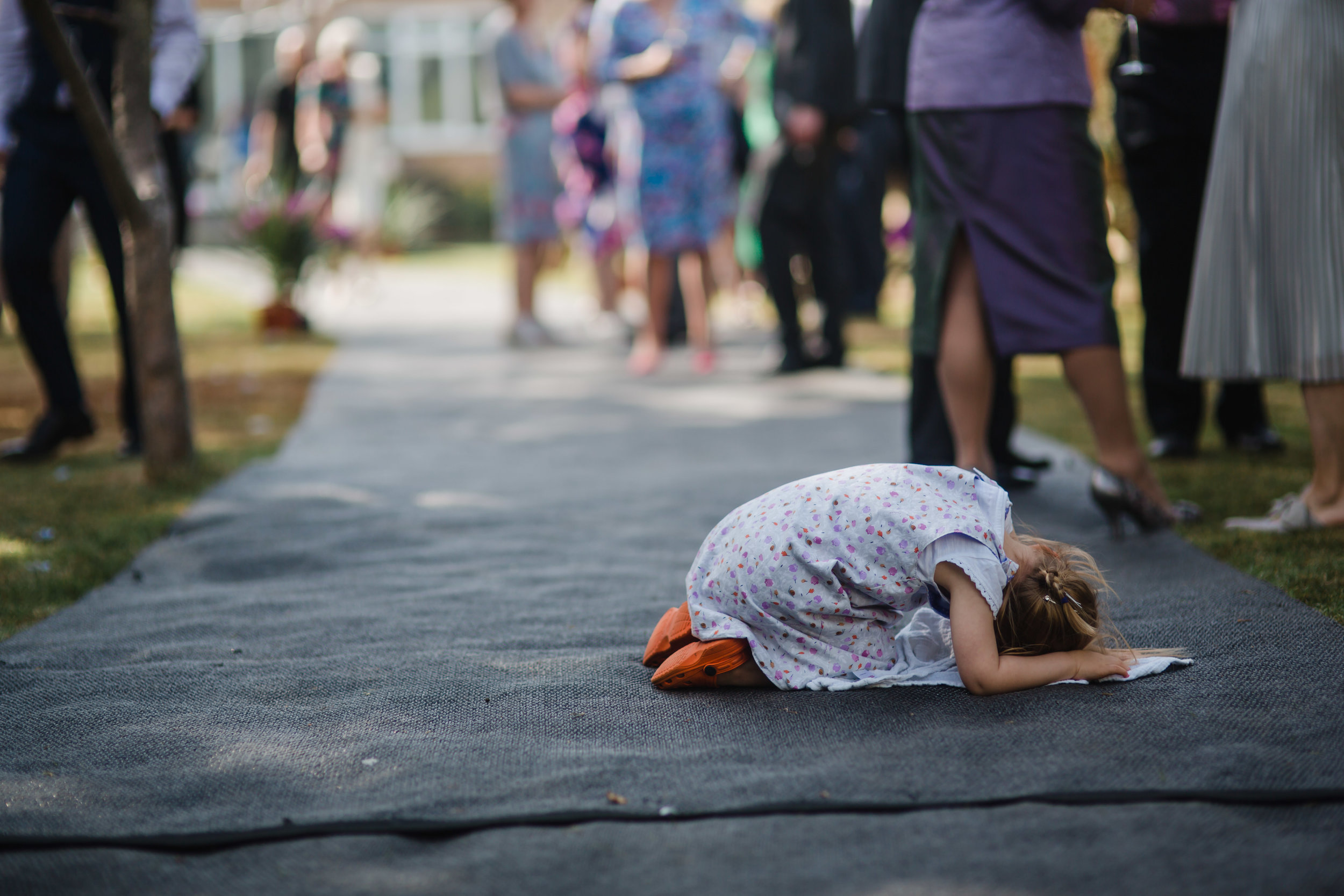 a child cries on the floor at a wedding
