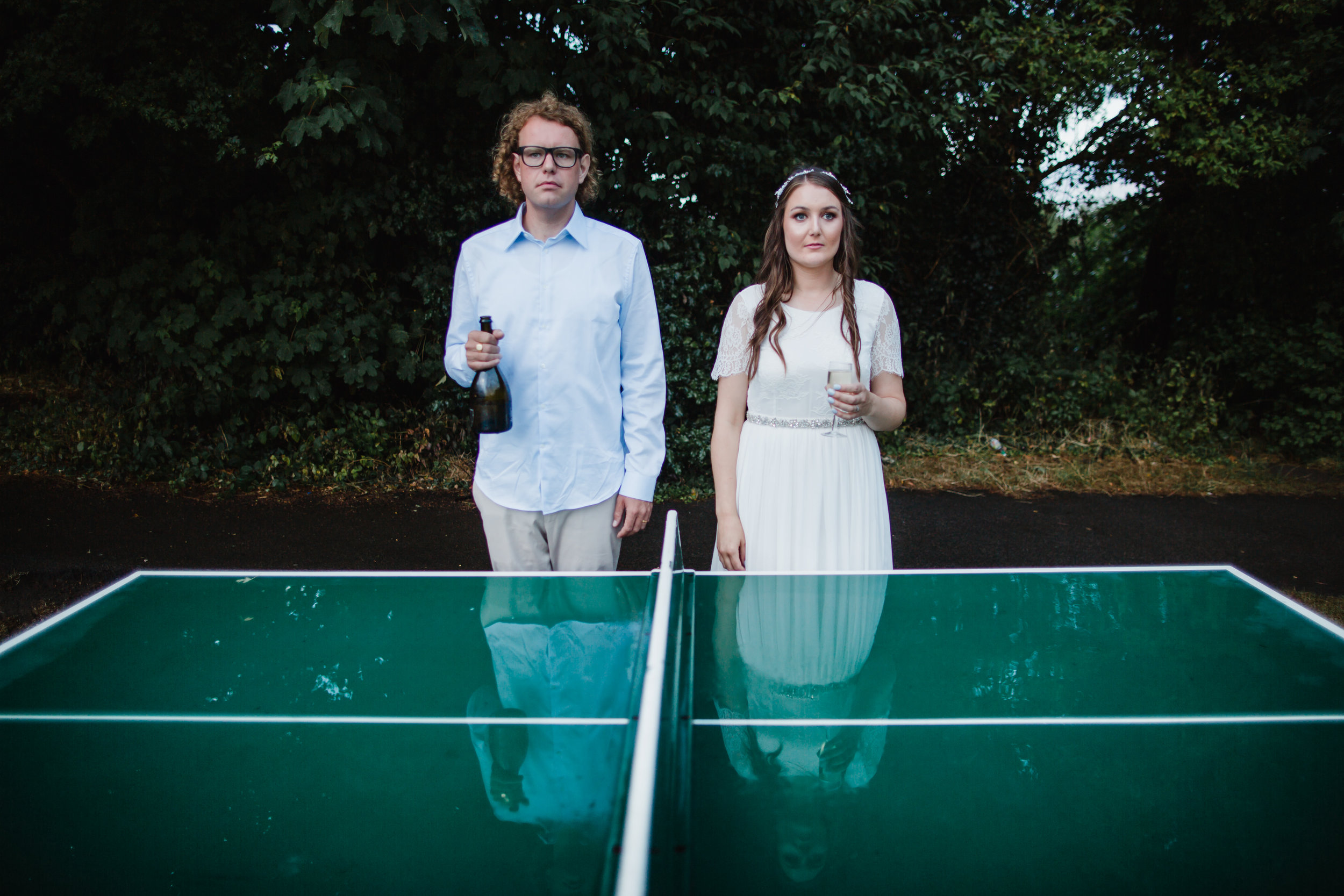 a bride and groom pose in front of a table tennis table